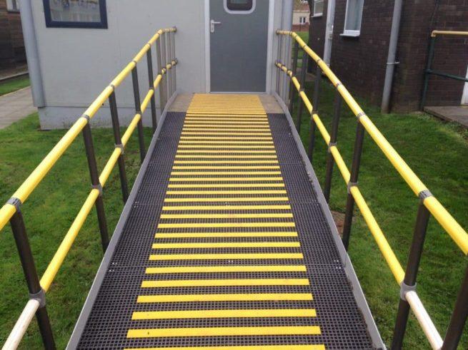 Les lames antidérapantes grp jaune ont été fixés sur une rampe d'accès pour personne à mobilité réduite