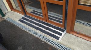 Plaque antidérapante posée devant une porte d'entrée d'un établissement