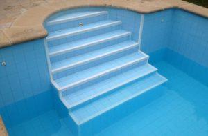 Nez de marche antidérapant blanc sur les marches d'une piscine