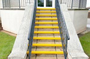 Nez de marche antidérapant jaune sur les marches d'un escalier en extérieur