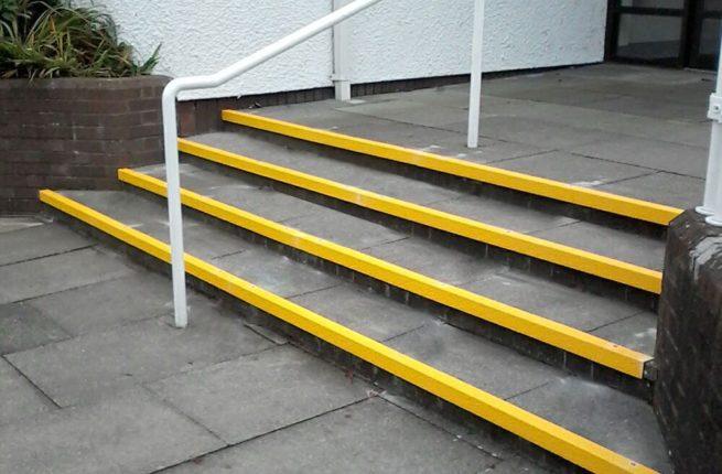 Nez de marche antidérapant jaune sur les marches d'un escalier devant une résidence